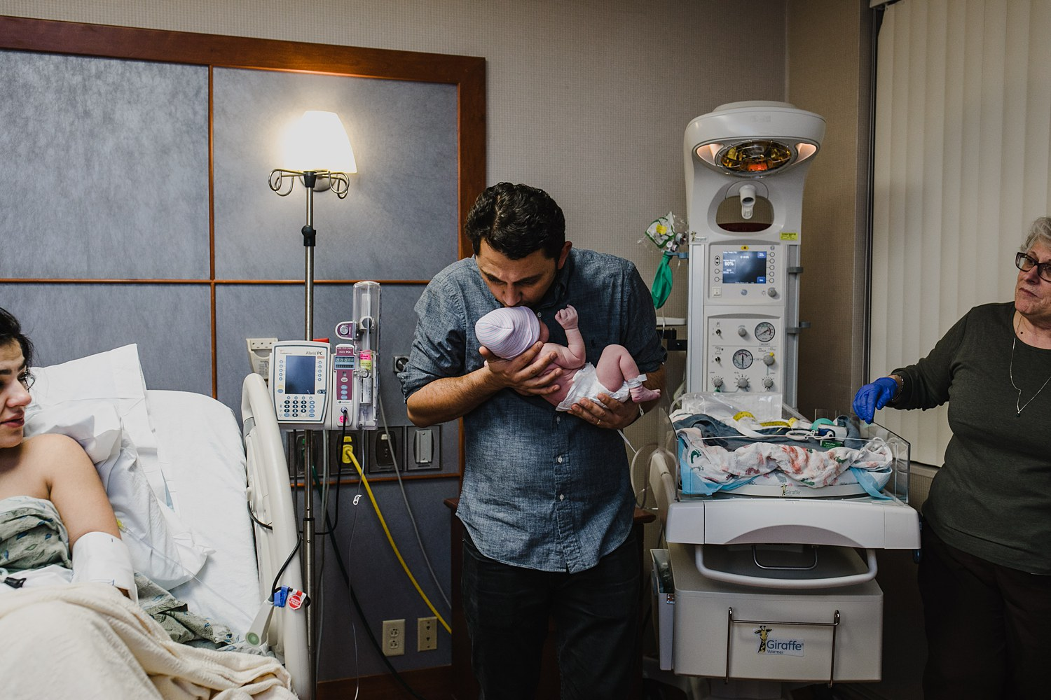 New Father kisses his newborn daughter for the first time after her birth in the East Bay of the San Francisco's Bay Area.