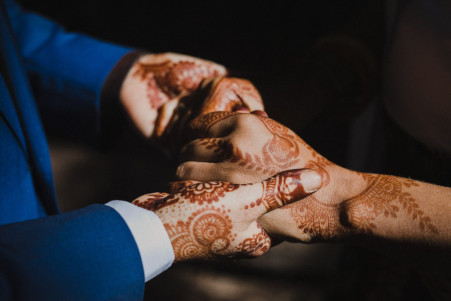 Same sex couple hold hands decorated in wedding henna.