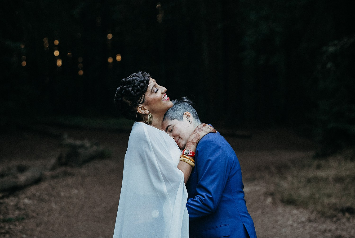 Recently married couple embraces after their wedding in Joaquin Miller Park