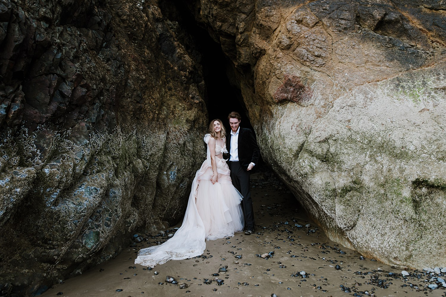 Newlywed couple laughs inside a cave on the beautiful Oregon coastline.