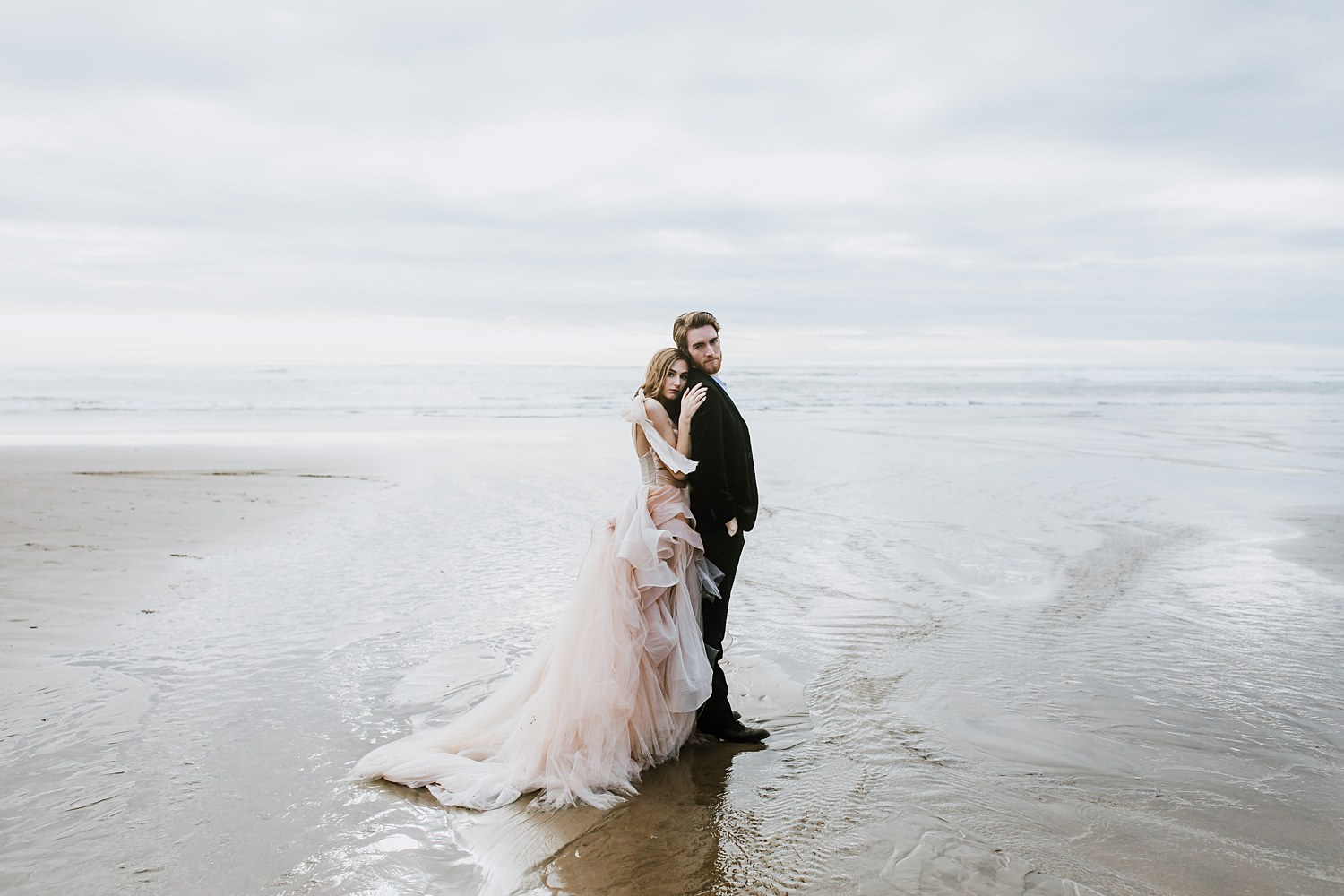 Newlywed couple hold each other close on an Oregon coast beach wearing a Claire La Faye wedding dress