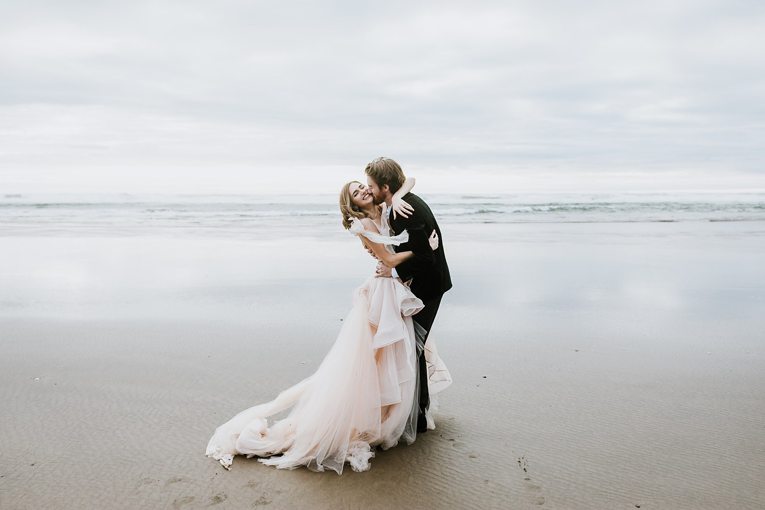 Newlywed couple embraces on the Oregon Coast