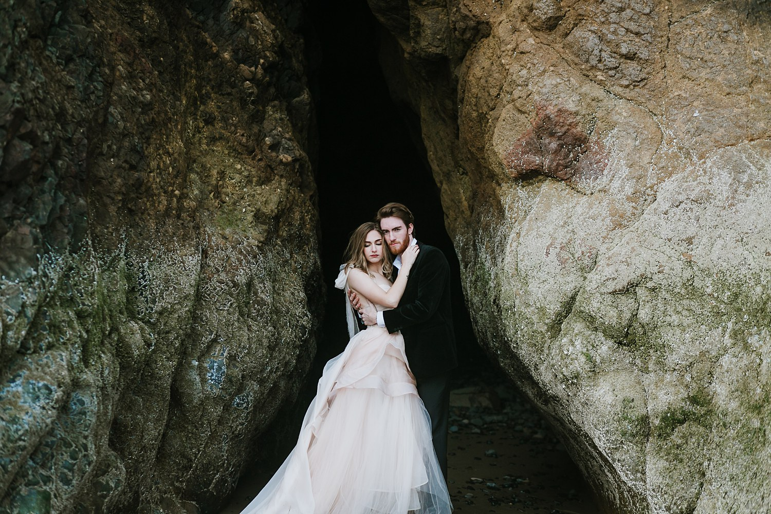 Newlywed couple hugs in a beautiful cave at Canon Beach, Oregon.